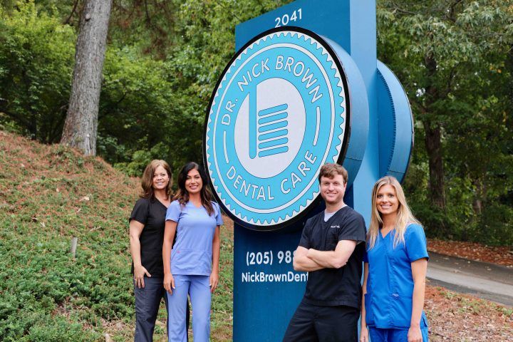 Dr. Nick Brown Dental Care Staff in front of Sign